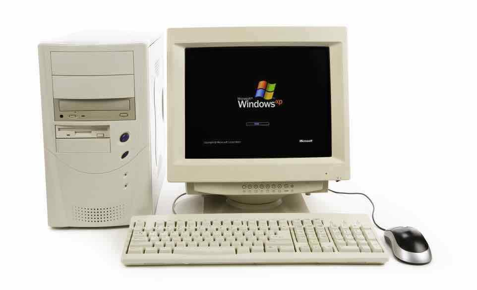 Old desktop PC with old fashioned monitor showing the Windows XP startup screen