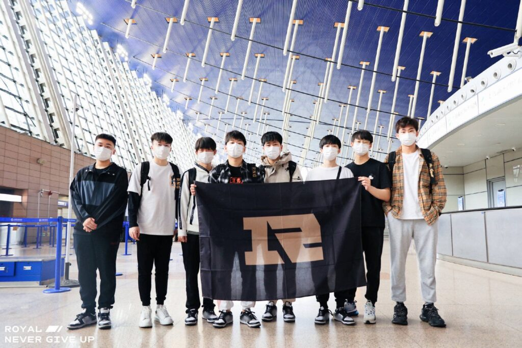 RNG members at the airport carrying their team banner   Riot Games 2021